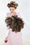 Pretty Woman With Ostrich Feather Duster. Portrait of happy young woman with hair curlers holding an ostrich feather duster Royalty Free Stock Images