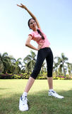 Pretty woman outdoors exercise at park. With smile Stock Photos