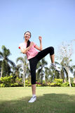 Pretty woman outdoors exercise at park. With side kicks Royalty Free Stock Photography