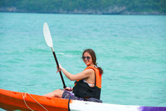 Pretty woman with a paddle kayaking on the sea Royalty Free Stock Photo
