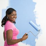 Pretty woman painting wall. Royalty Free Stock Photos
