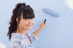 Pretty woman painting wall blue and smiling at camera. In new home Stock Images