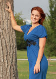 Pretty Woman in Park. Portrait of pretty woman leaning against a tree at the park Stock Image