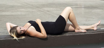 Pretty woman in the park. Woman laying on stage of an ampitheatre in the park Royalty Free Stock Photography