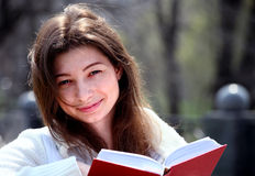 Pretty woman in park reading book and smiling Stock Images