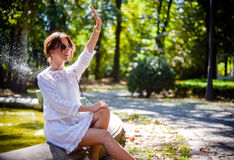 Pretty Woman at the Park Waving to Someone Stock Image