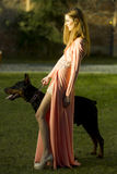 Pretty woman in peach dress with mastiff. Attractive young woman with thoroughbred mastiff standing in profile on green lawn with fresh grass looking away in royalty free stock photos