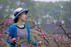 Pretty woman and peach flowers Stock Image