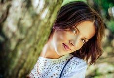 Pretty Woman Peeking From Behind a Tree Royalty Free Stock Photo
