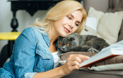 Pretty woman petting her cat Stock Image