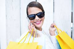 Pretty woman on the phone holding shopping bags Royalty Free Stock Image