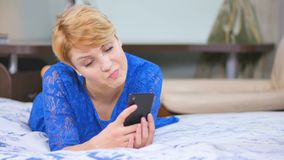 Pretty woman with phone laying on the bed. Beautiful woman lays on the bed. Pretty female in blue dress in bedroom on the bed. Young woman relaxing at home. The stock footage
