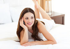 Pretty woman on phone lying on bed Stock Image