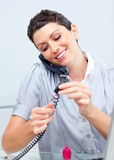 Pretty woman on phone painting her nails Royalty Free Stock Image