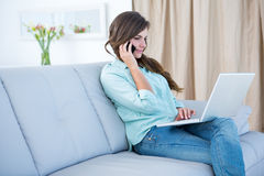 Pretty woman on the phone using her laptop Stock Photos