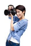 Pretty woman-photographer takes snapshots. Woman takes images holding photographic camera, isolated on a white royalty free stock images