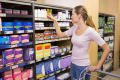 Pretty woman picking product in shelf Royalty Free Stock Photos