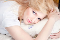 Pretty woman on pillow. Pretty blond woman with blue eyes on pillow Royalty Free Stock Photos