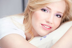 Pretty woman on pillow. Pretty blond woman with blue eyes on pillow Royalty Free Stock Image