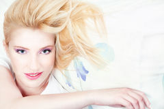 Pretty woman on pillow. Pretty blond woman with blue eyes on pillow Royalty Free Stock Images
