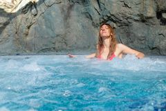 Pretty woman in pink bikini relaxes in a hot tub stock photo