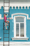 Pretty woman in pink on fire escape stair Royalty Free Stock Images