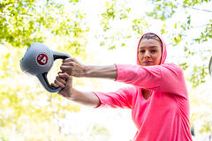 A pretty woman in a pink outfit doing exercise with a weight Stock Photography