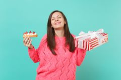 Pretty woman in pink sweater with closed eyes holding eclair cake, red present box with gift ribbon isolated on blue. Background. Valentine`s, Women`s Day royalty free stock image