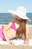 Pretty woman in pink swimsuit lying on the beach Royalty Free Stock Photo