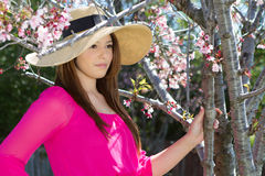 Pretty Woman in Pink under cherry blossoms wearing a hat Royalty Free Stock Photography