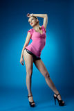 Pretty woman pinup portrait in pink dress on blue Royalty Free Stock Images