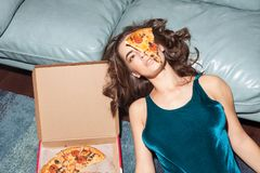 Pretty woman with pizza on her face. Sexy woman lies with pizza on her face indoor, home interior Stock Photography