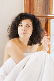 Pretty woman play with hair between bedclothes Stock Photo