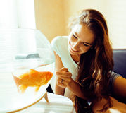 Pretty woman playing with goldfish at home, sunlight morning happy lifestyle Royalty Free Stock Photos