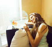 Pretty woman playing with goldfish at home, sunlight morning Stock Image