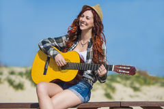 Pretty woman playing a guitar Royalty Free Stock Photo