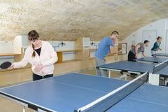 Pretty woman playing ping-pong with friends royalty free stock image