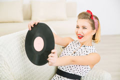 Pretty woman playing with vinyl record. Royalty Free Stock Photography