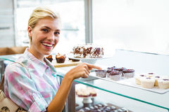 Pretty woman pointing at cup cakes Stock Photo