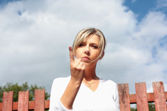 A pretty woman with pointing finger. Focus on the face Stock Images