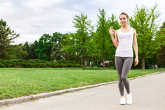 Pretty woman pointing ok in park Royalty Free Stock Photos