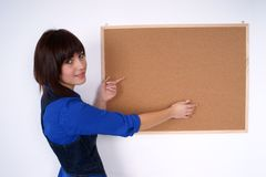 Pretty woman pointing at the pin board. Royalty Free Stock Photography