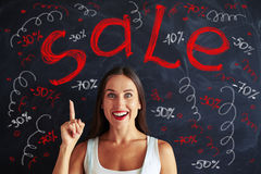 Pretty woman pointing up with her finger at sale advertisement o Stock Photo