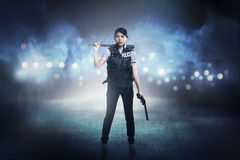 Pretty woman in police vest holding baseball bat. As weapon Stock Photos