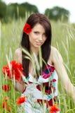 Pretty woman in poppy flowers Stock Photography