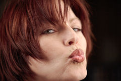 Pretty woman portrait. Pretty  girl is blowing kiss over black background Royalty Free Stock Photo