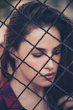 Pretty woman portrait behind fence shot in the city Stock Photography