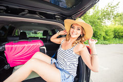 Pretty woman portrait at the car trunk with suitcases Royalty Free Stock Photo