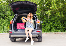 Pretty woman portrait at the car trunk with suitcases Royalty Free Stock Photos