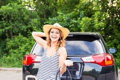 Pretty woman portrait at the car trunk with suitcases Stock Photos